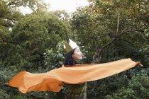 Seitenansicht einer Frau mit Krone und orangefarbenem Schal, die im Park posiert — Stockfoto