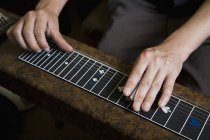 Crop male hands playing slide guitar — Stock Photo