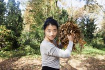 Portrait of woman standing at park and preparing to throw dry leaves at camera — Stock Photo