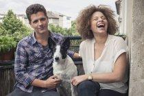 Счастливые молодые друзья сидят с собакой на балконе — стоковое фото