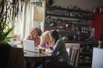 Lächelnde Freundinnen mit Laptop am Fenster — Stockfoto