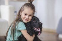 Портрет улыбающейся девушки, обнимающей Кокер-спаниеля дома и смотрящей в камеру — стоковое фото