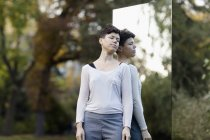 Ritratto di donna con gli occhi chiusi appoggiata sullo specchio al parco — Foto stock