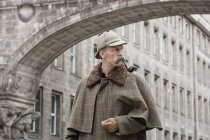 Man dressed up as Sherlock Holmes standing under a building arch and looking away — Stock Photo
