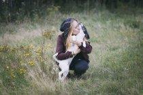 Женщина сидит на травянистом поле и гладит маленькую собачку — стоковое фото