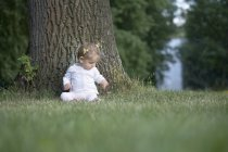 A baby girl sitting under a tree — Stock Photo