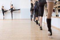 Geringen Teil der Ballerinas stehen auf einem Bein im Tanzstudio — Stockfoto