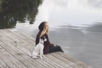 Thoughtful woman sitting with dog on jetty over lake and looking away — Stock Photo