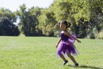 Petite fille en costume de fée courir sur la cour — Photo de stock