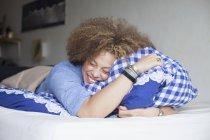 Donna felice con gli occhi chiusi sdraiato sul letto e tenendo cuscino — Foto stock