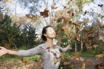 Dry leaves falling on happy woman standing with arms outstretched at park on autumn day — Stock Photo