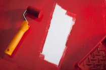 Paint roller painting background in red — Stock Photo