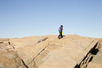 Person hiking over rocks against clear sky — Stock Photo