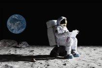 Vista lateral do astronauta sentado na rocha e usando laptop — Fotografia de Stock