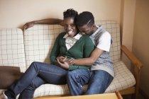 Retrato de joven cariñosa pareja relajante en el sofá - foto de stock
