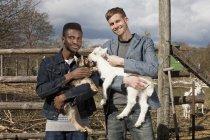 Retrato de dois amigos do sexo masculino segurando cabras criança no campo — Fotografia de Stock