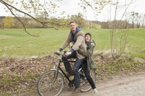 Man riding bicycle with girlfriend in countryside — Stock Photo