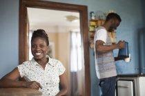 Портрет молодой женщины, сидя на кухне с молодым человеком на фоне — стоковое фото