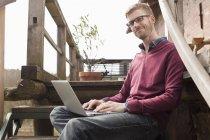 Retrato de homem com laptop sentado na escada de madeira — Fotografia de Stock