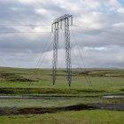 Pylône électrique sur champ vert au temps nuageux — Photo de stock