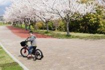 Retrato de longitud completa de bicicleta de niño montar a caballo en el sendero en el Parque - foto de stock
