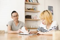Young woman writing in notebook by man at home — Stock Photo