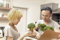 Smiling young couple removing fresh vegetables from cardboard box — Stock Photo
