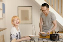 Happy young couple enjoying food on dining table at home — Stock Photo