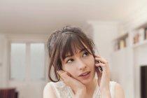 Mujer joven mirando hacia otro lado mientras habla en el teléfono móvil en casa - foto de stock