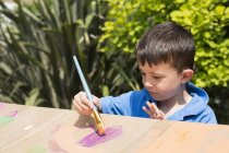 Cute boy painting on cardboard playhouse in back yard during — Stock Photo