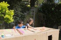 Crianças pintando cartolina playhouse no quintal no dia ensolarado — Fotografia de Stock