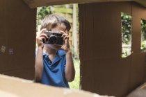 Мальчик фотографирует через картонный домик — стоковое фото