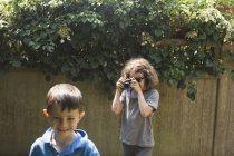 Girl photographing friend in back yard — Stock Photo