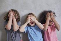 Fröhliche Mädchen Augen mit bemalten Händen stehend gegen graue Wand bedecken — Stockfoto