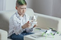 Мальчик, сидящий на диване с дроном на столе и с дистанционным управлением — стоковое фото