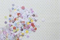 Directement au-dessus de la photo de plusieurs boutons colorés sur le tissu — Photo de stock