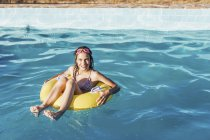 Full length portrait of happy girl in inflatable ring on swimming pool — Stock Photo