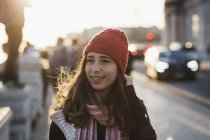 Smiling woman wearing knit hat walking in city during sunset — Stock Photo