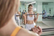 Determined young woman exercising with barbell in health club — Stock Photo