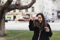 Donna felice fotografare da smart phone tenendo bevanda — Foto stock