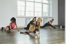 Confident young women practicing splits while dancing in studio — Stockfoto