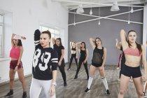 Уверенные женщины, протягивающие руки во время танцев в студии — стоковое фото