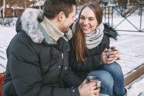 Glückliches Paar sitzt mit Getränken auf der Promenade und schaut sich an — Stockfoto