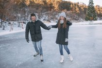 Пара, взявшись за руки во время катания на коньках на катке — стоковое фото