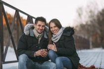 Ritratto delle coppie felici che si siede con bevande sulla passerella durante giorno di inverno — Foto stock