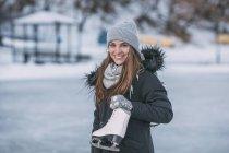Портрет усміхнений молода жінка, стоячи з льоду кататися на ковзанах — стокове фото