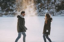 Side view of playful man and woman throwing snow — Stock Photo