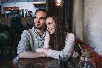Joyeux jeune couple regardant loin tout en étant assis au café — Photo de stock