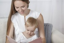 Smiling mother and daughter reading picture book sitting on sofa at home — Stock Photo