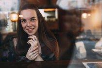 Lächelnde junge Frau durch Café Fenster gesehen — Stockfoto
